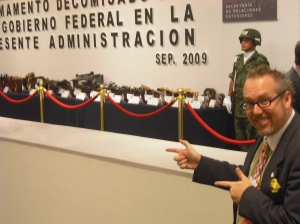 Peace Action Organizing and Policy Director Paul Kawika Martin points to weapons confiscated by the Mexican goverment (this display was in the Foreign Ministry right next to our conference!)