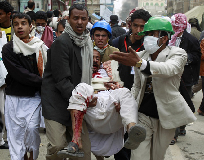 Anti-government protesters carry an injured fellow protester in Sanaa