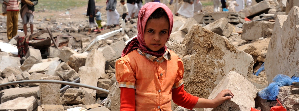 epa04783119 A young Yemeni poses in front of the ruins of his family house a day after it was destroyed by an airstrike carried out by the Saudi-led coalition in Sana?a, Yemen, 04 June 2015. According to reports Yemenis are marking International Day of Innocent Child Victims of Aggression, observed on 04 June each year in order to acknowledge the pain suffered by children caught in violent conflict throughout the world.  EPA/YAHYA ARHAB